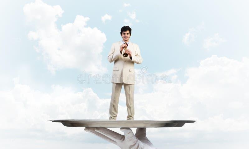 Zakenman die op metaaldienblad Fife spelen tegen blauwe hemelachtergrond stock foto
