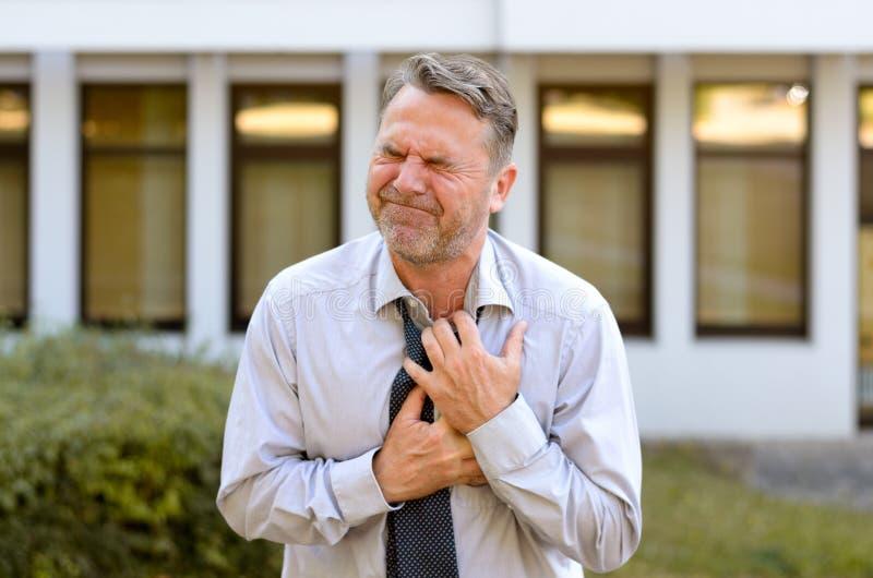 Zakenman die op middelbare leeftijd borst aan pijnen lijden stock foto