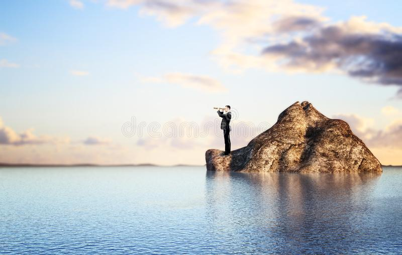Zakenman die op rots de afstand onderzoeken stock afbeeldingen