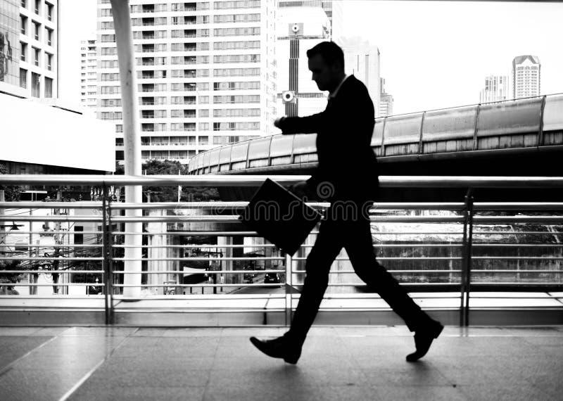 Zakenman die op skywalk haastig lopen In zijn hand is een zwarte leeraktentas Met gloedlicht stock afbeelding