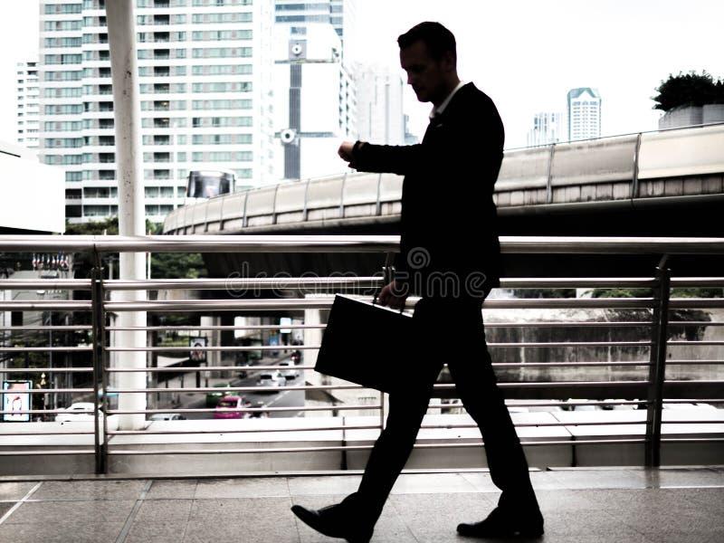 Zakenman die op skywalk haastig lopen In zijn hand is een zwarte leeraktentas Met gloedlicht royalty-vrije stock fotografie