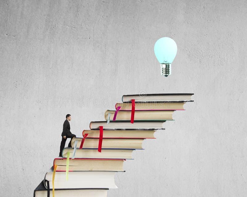 Zakenman die op stapel boeken beklimmen om bovenkant met bol te bereiken stock afbeeldingen