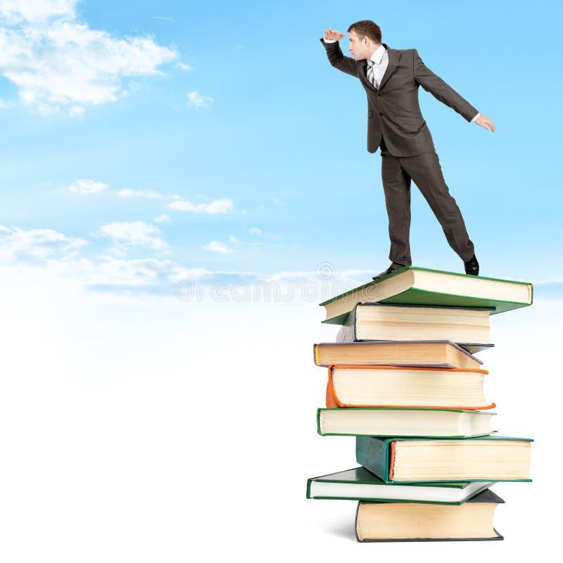 Zakenman die op stapel van boeken onder wolken blijven royalty-vrije stock afbeelding
