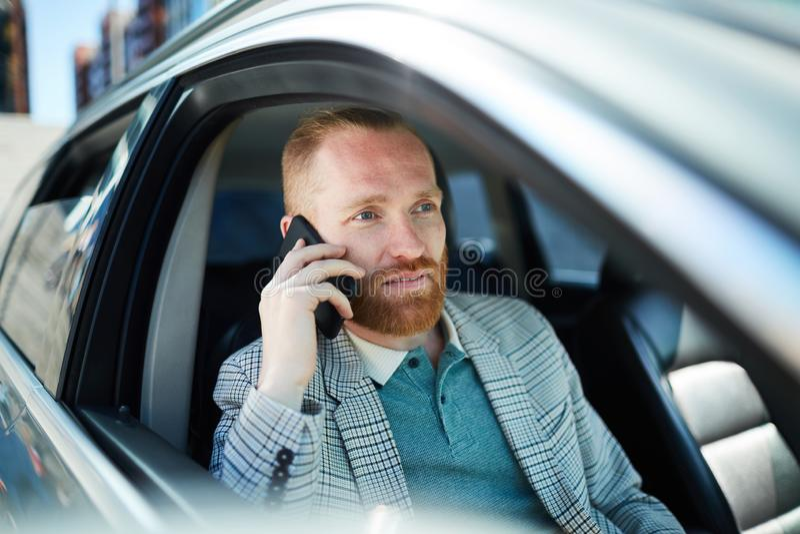 Zakenman die op telefoon in auto spreken stock foto
