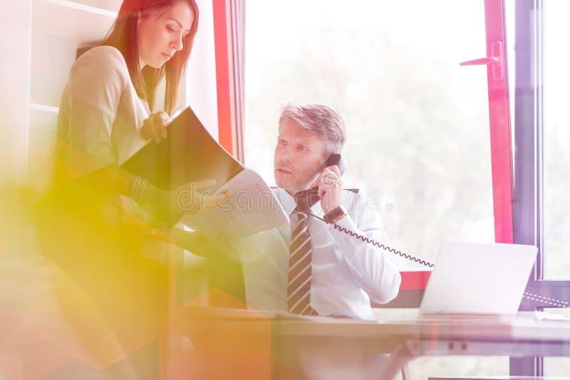 Zakenman die op telefoon spreken terwijl het controleren van documenten met collega in bureau royalty-vrije stock foto