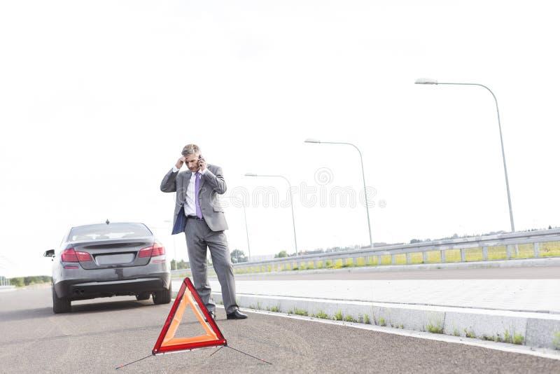 Zakenman die op telefoon spreken terwijl status met analyseauto door waarschuwingsbord op weg stock fotografie