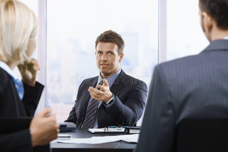Zakenman die op vergadering spreekt royalty-vrije stock afbeelding