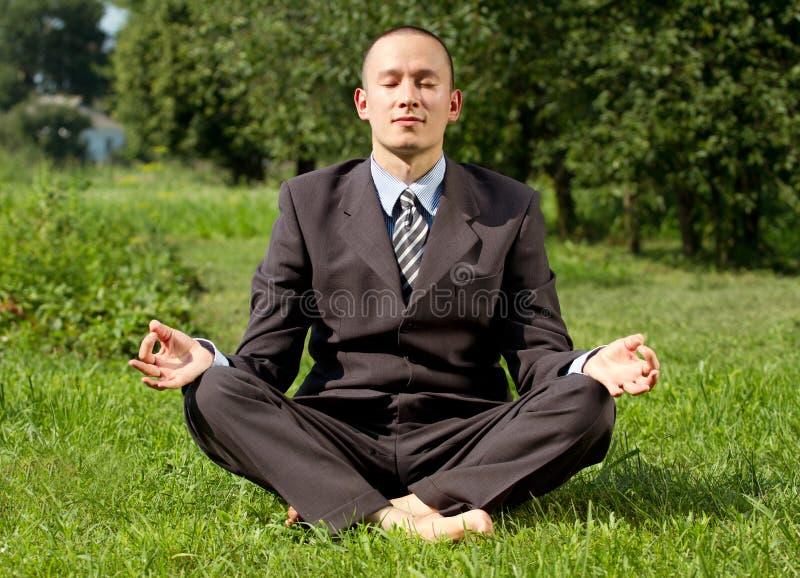 Zakenman die in openlucht mediteert stock afbeeldingen