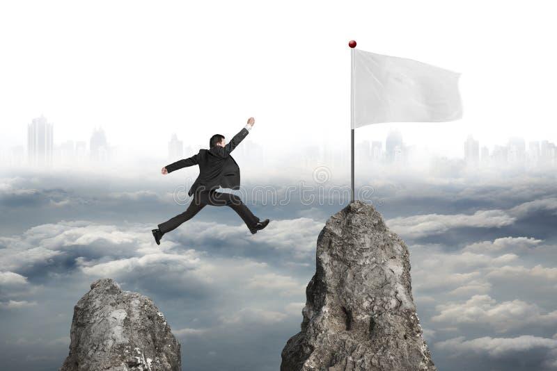 Zakenman die over bergpiek aan vlag met bewolkte citys springen royalty-vrije stock afbeeldingen