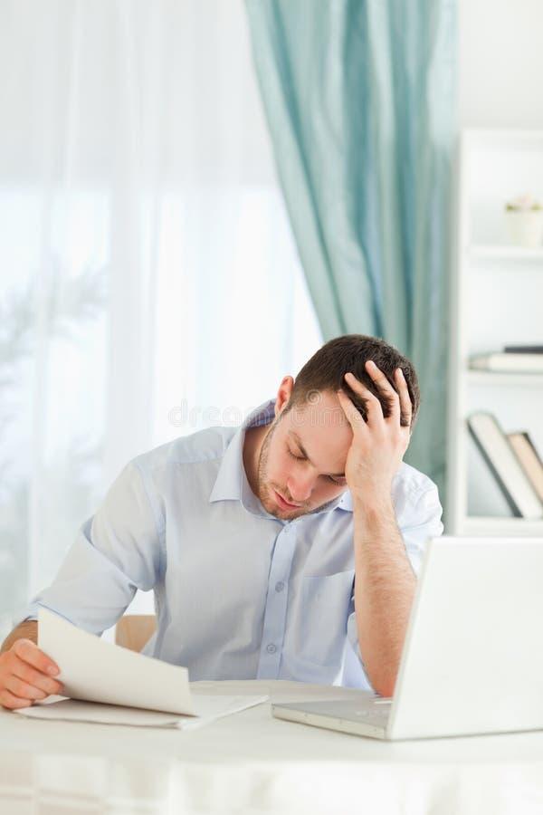 Zakenman die over een brief ongerust wordt gemaakt stock fotografie