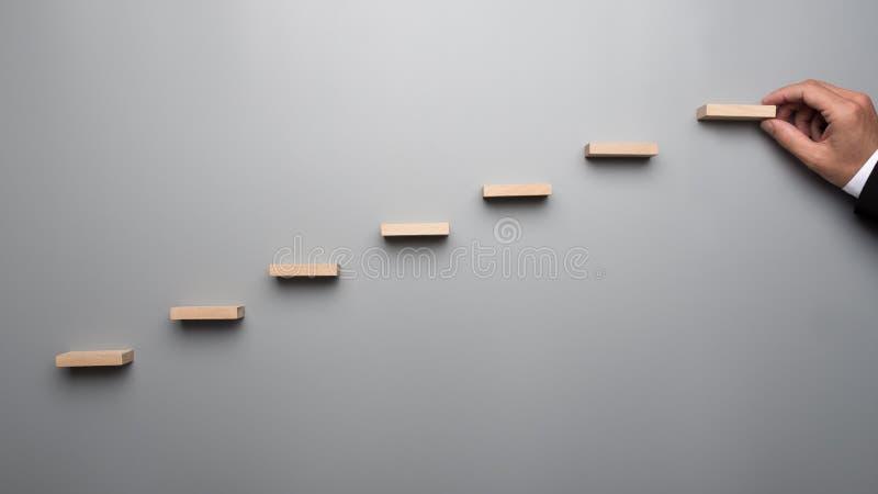 Zakenman die in pak een grafiek of een ladder van succe bouwen stock foto