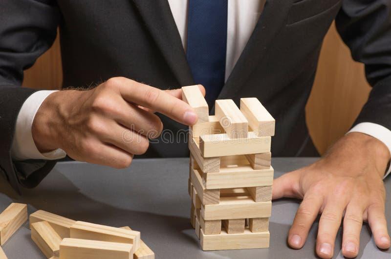 Zakenman die in pak een toren van houten blokken, strategie en planning in zaken bouwen royalty-vrije stock fotografie