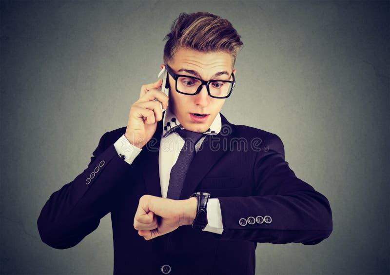 Zakenman die polshorloge bekijken, die op mobiele telefoon spreken die laat voor vergadering lopen De tijd is geld stock afbeeldingen