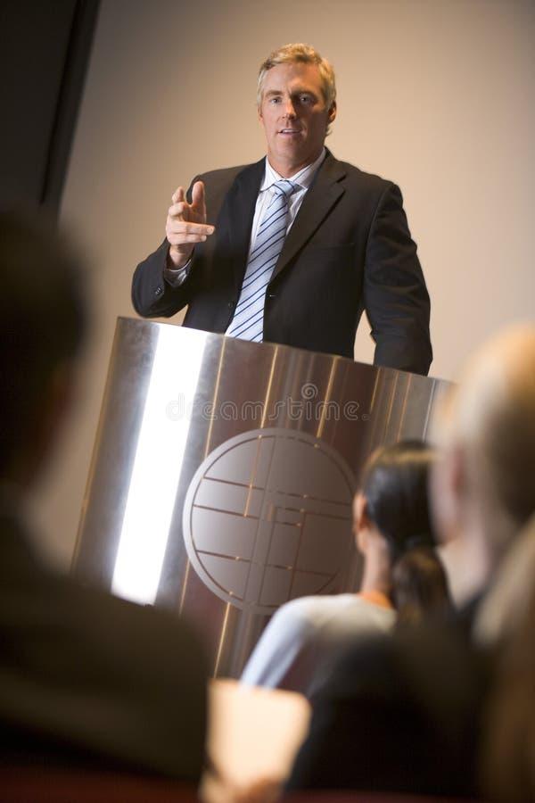 Zakenman die presentatie geeft bij podium stock foto