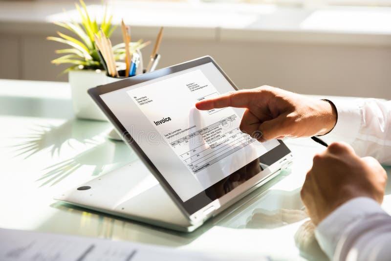 Zakenman die rekening op laptop onderzoeken stock afbeelding