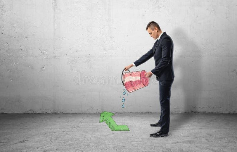 Zakenman die rode emmer met water het uitgieten van het op groene pijl houden die benadrukken royalty-vrije stock afbeelding