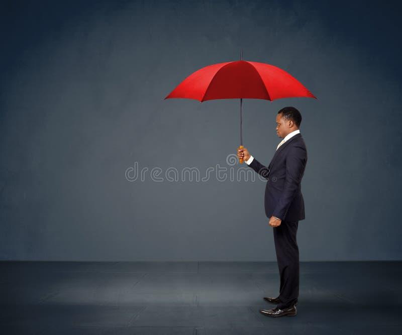 Zakenman die rode paraplu houdt stock foto's