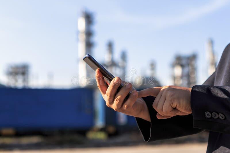 Zakenman die rond de installatie van de olieraffinaderij met duidelijke hemel controleren stock foto