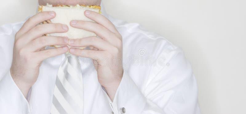 Zakenman die sandwich eet stock foto's