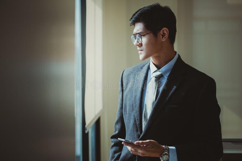 Zakenman die slimme telefoon in bureau houden Het concept van de planning stock afbeelding