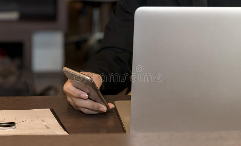 Zakenman die slimme telefoon en tabletcomputer met behulp van aan het werk met financiële gegevens stock afbeelding