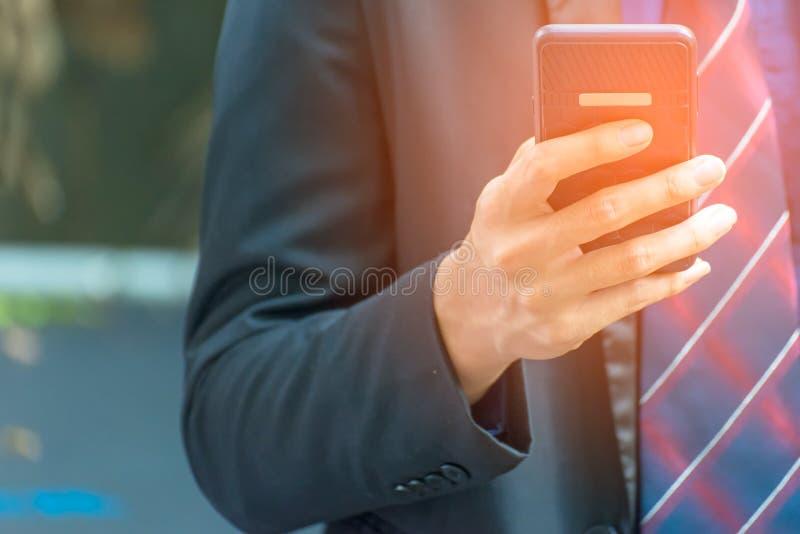 Zakenman die slimme telefoon met behulp van aan het werk met financiële gegevens in stad royalty-vrije stock foto