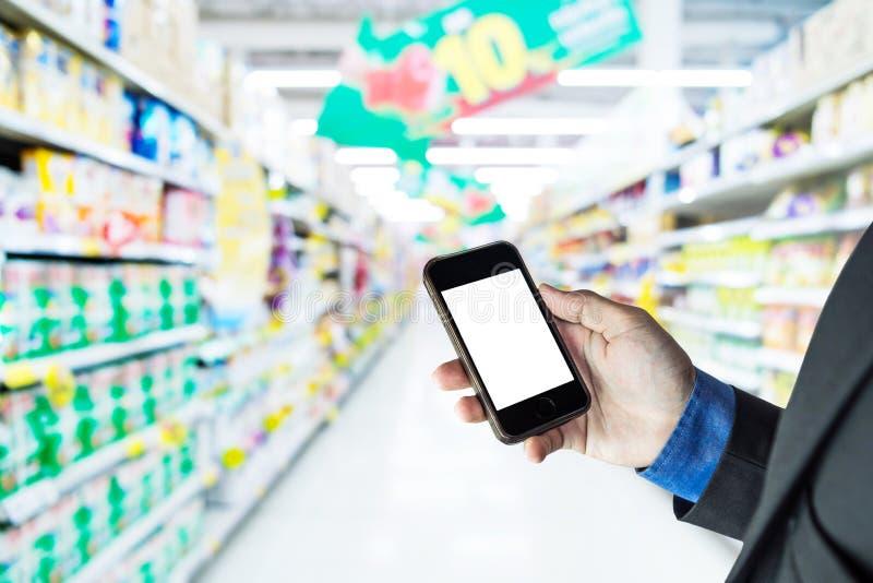 Zakenman die slimme telefoon, op de achtergrond van de supermarktdoorgang houden stock fotografie