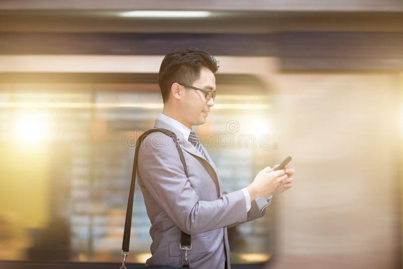 Zakenman die smartphone gebruiken bij metropost royalty-vrije stock foto's