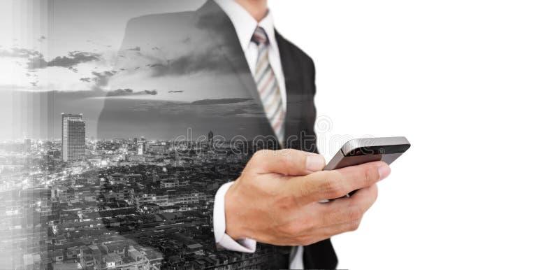 Zakenman die smartphone met dubbele cityscape van de blootstellingswolkenkrabber, met witte exemplaarruimte gebruiken stock afbeelding
