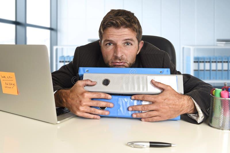 Zakenman die in spanning bij bureaulaptop computer werken die uitgeput en overweldigd kijken royalty-vrije stock afbeeldingen