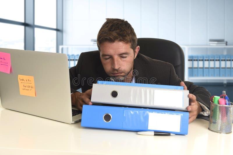 Zakenman die in spanning bij bureaulaptop computer werken die uitgeput en overweldigd kijken stock afbeelding