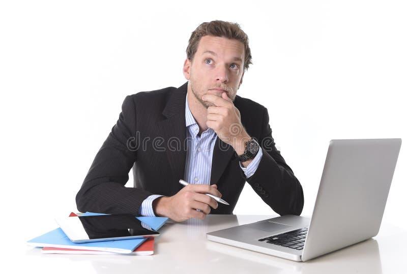 Zakenman die in spanning bij laptop van de bureaucomputer wederkerende en twijfelachtige peinzend werken en nadenkend royalty-vrije stock afbeeldingen