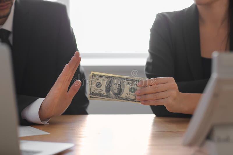 Zakenman die steekpenning bij lijst weigeren te nemen Het concept van de corruptie royalty-vrije stock foto
