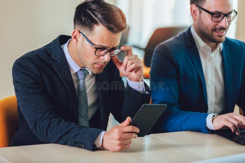 Zakenman die tablet in bureau gebruiken stock foto
