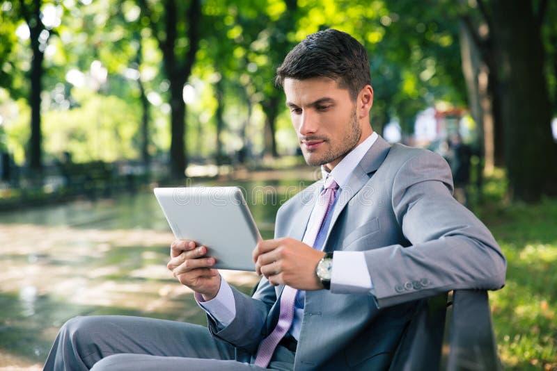 Zakenman die tabletcomputer in openlucht met behulp van royalty-vrije stock foto