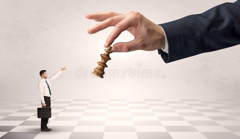 Zakenman die tegen groot schaakstuk op een grote hand vechten stock fotografie
