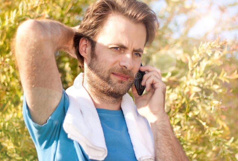 Zakenman die telefoongesprek ontvangen tijdens openluchttraining stock foto