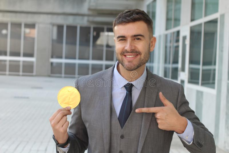 Zakenman die terwijl het houden van een Bitcoin glimlachen stock afbeeldingen