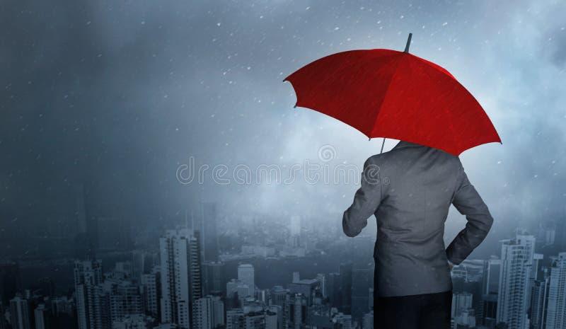 Zakenman die terwijl het houden van een rode paraplu over onweer op reusachtige regenachtergrond bevinden zich royalty-vrije stock foto