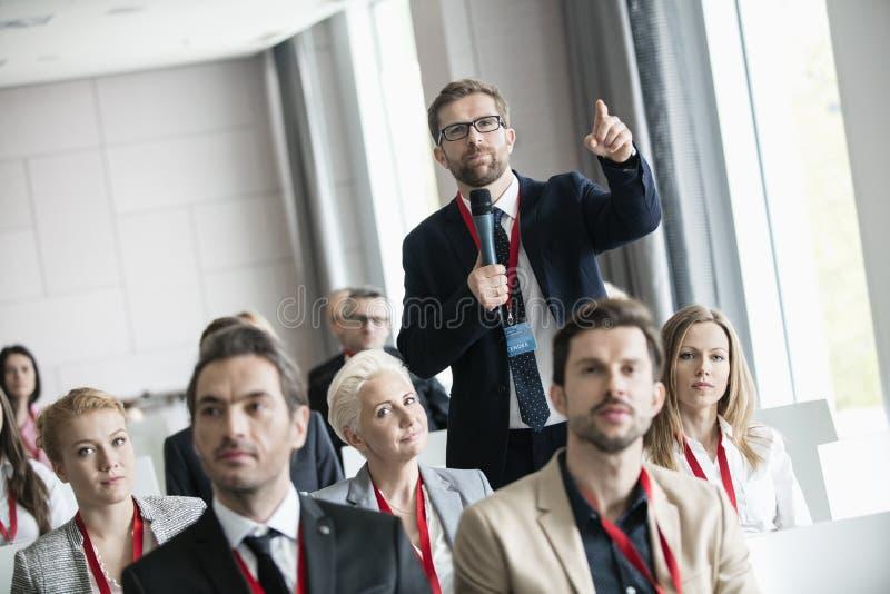 Zakenman die terwijl het stellen van vraag tijdens seminarie in overeenkomstcentrum gesturing royalty-vrije stock fotografie