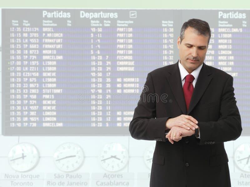 Zakenman die tijd controleert op zijn horloge stock afbeeldingen