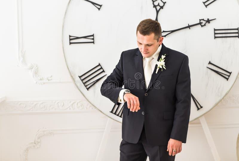 Zakenman die tijd controleren op zijn horloge royalty-vrije stock afbeelding