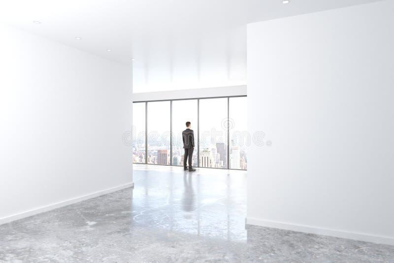 Zakenman die uit het venster in leeg bureau met beton kijken stock foto's