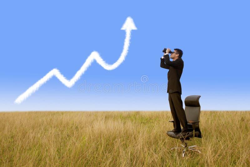 Zakenman die verrekijkers met behulp van die de wolk van de de groeigrafiek kijken royalty-vrije stock afbeeldingen