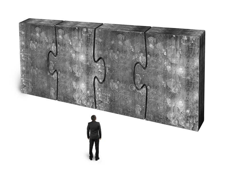 Zakenman die vier reusachtige concrete samen verbonden raadsels onder ogen zien stock fotografie