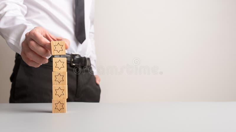 Zakenman die vijf houten kubussen met sterren op hen stapelen stock afbeeldingen