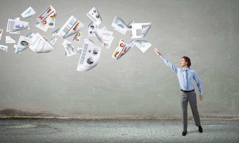Zakenman die vliegende documenten vangen royalty-vrije stock afbeeldingen