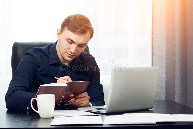 Zakenman die in vrijetijdskleding nota's schrijven aan zijn agenda royalty-vrije stock afbeeldingen