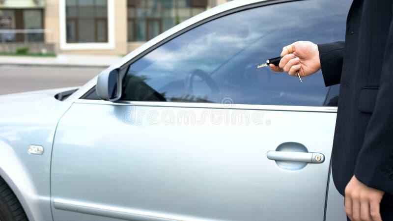 Zakenman die weg autoalarm veranderen, die in auto, veiligheidssysteem, verzekering krijgen stock foto