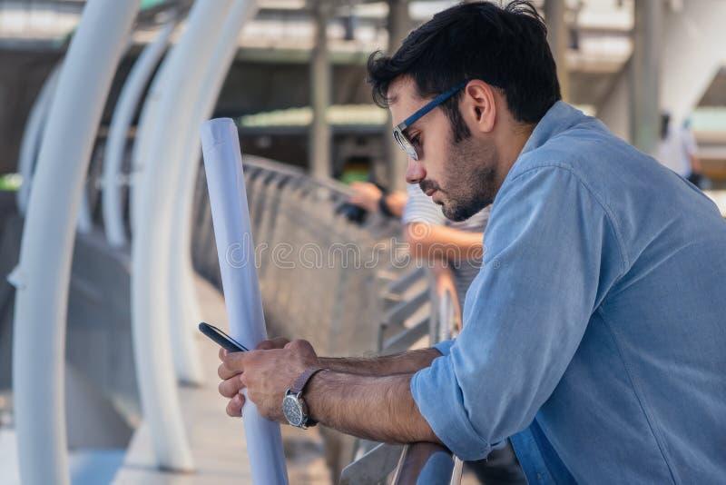 Zakenman die zich bij buitencoridor bevinden gebruikend smartphone met één de ingenieursplan van de handgreep royalty-vrije stock foto